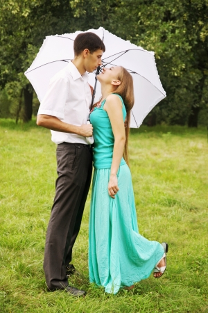 couple in rain: Loving couple kissing under a white umbrella