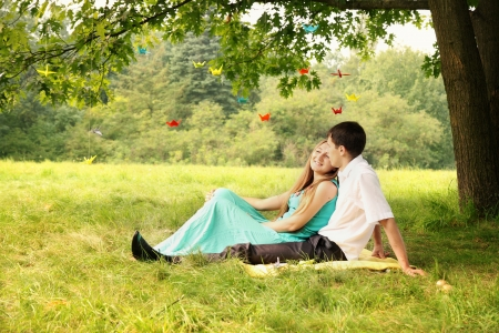 young couple sitting under a tree hugging