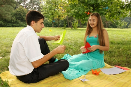 young couple making origami at a picnic in the park photo