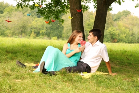 Young couple relaxing on the grass under a tree photo
