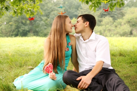 gentle kiss of a young couple on a picnic photo