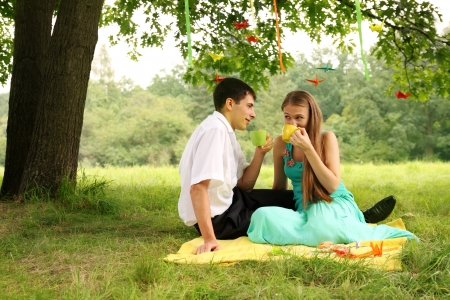Couple drinking tea in the park under a tree photo