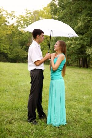 uomo sotto la pioggia: Amare coppia in piedi sotto un ombrello bianco Archivio Fotografico