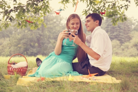 Young couple drinking wine under a tree photo