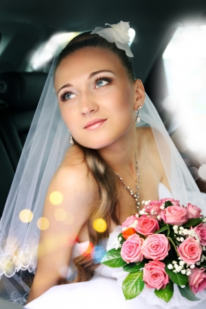 Dreamy beautiful bride sitting in the car photo