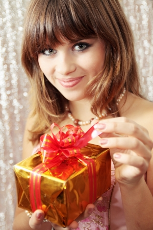 Young woman opens a box with a gift photo