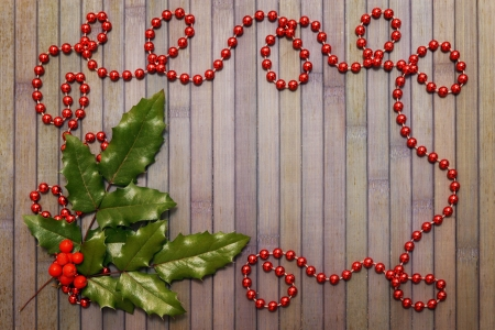 Christmas wooden background with garland and holly leaves photo