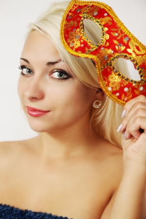 young woman holding a carnival mask in hand photo