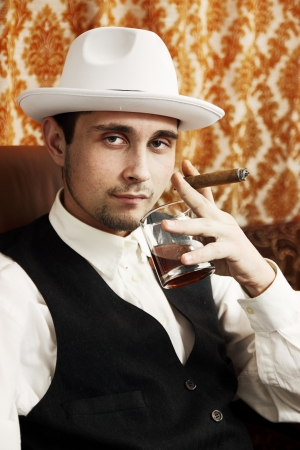 A young man with a cigar and a glass of whiskey Stock Photo - 16942350