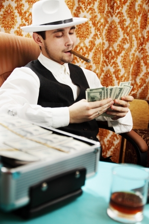 Mafia man with a cigar and a pack of money Stock Photo - 16942362