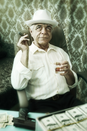 Old happy man pensively smoking a cigar photo