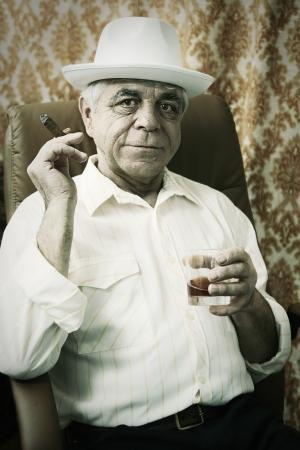 hombre fumando puro: Viejo hombre con un cigarro y whisky