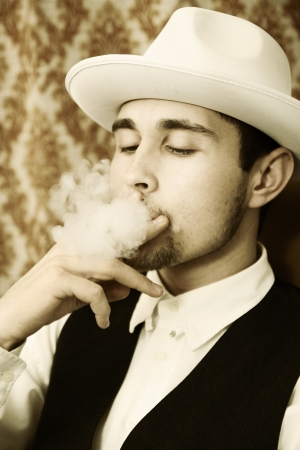 A young man in a hat with a cigar