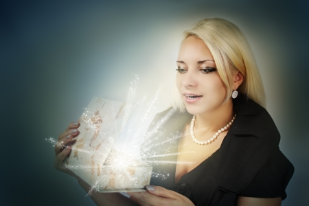 Young beautiful woman discovers a Christmas gift Stock Photo - 16949107
