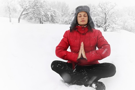 Woman meditating in the lotus position in winter