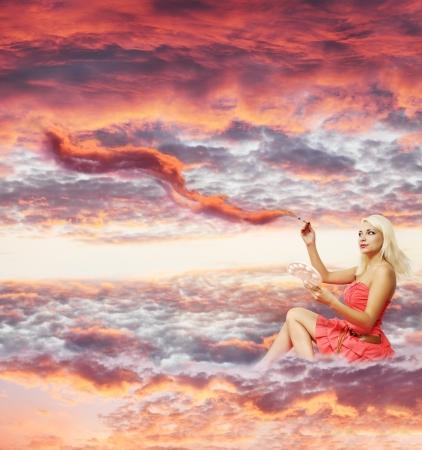 Collage, una donna su una nuvola con un pennello dipinge un tramonto Archivio Fotografico - 16942346