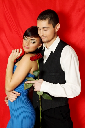Young couple with a rose on a red background Stock Photo - 17564876