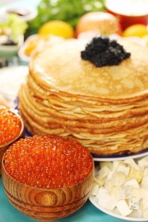 lot of red caviar in wooden plates with pancakes photo