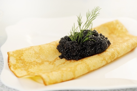 Ruddy pancake with black caviar and dill Stock Photo - 17882965