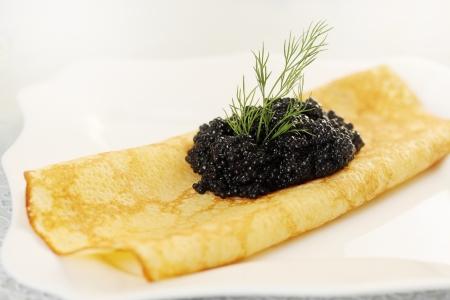 Ruddy pancake with black caviar and dill Stock Photo - 17882965