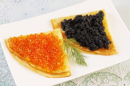thin pancakes with red and black caviar photo