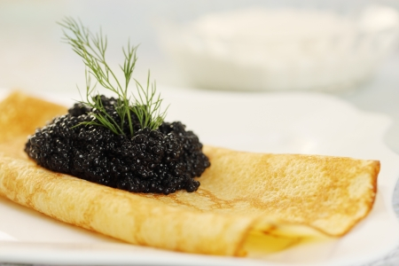 Ruddy pancake with black caviar and dill Stock Photo - 17882963