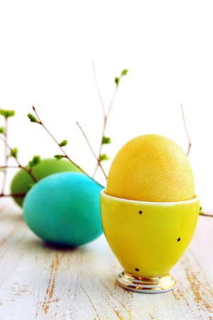 eggcup: yellow egg in a yellow ceramic stand on the board