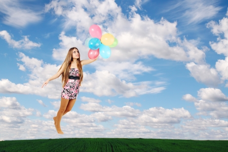 woman flies on the balloons in the clouds photo