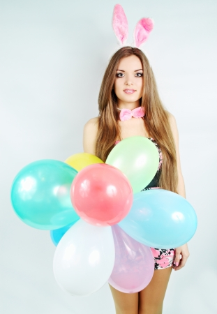 woman dressed as a rabbit holds balloons photo