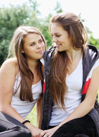 Two happy young girlfriends look at each other Stock Photo