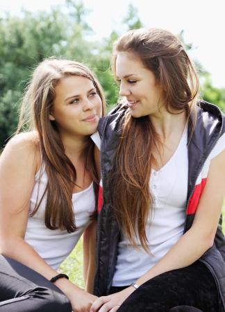 lesbische m�dchen: Zwei gl�ckliche junge Freundinnen schauen sich an Lizenzfreie Bilder