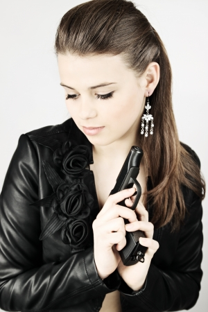 Young beautiful woman in a black jacket with a gun photo