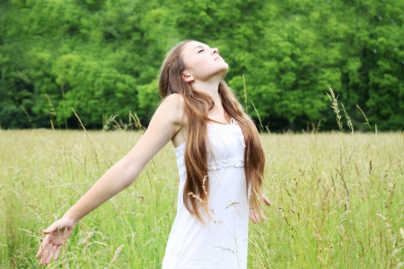 Free young woman on the meadow breathes in deeply