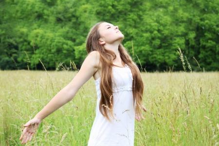 respiracion: Joven mujer libre en la pradera respira profundamente