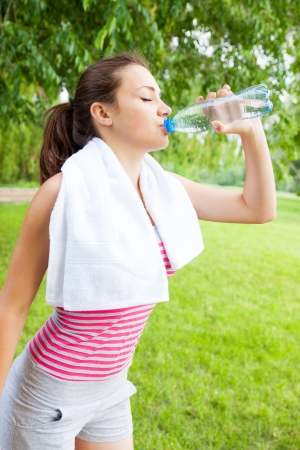 A woman drinks water from a bottle photo