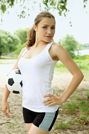 women playing soccer: Beautiful woman with a ball in her hands at the beach