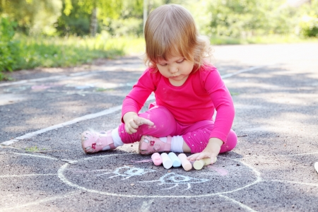 Little girl draws a large sun on asphalt photo