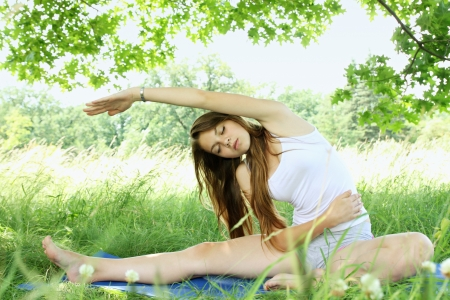Young woman in a park doing stretching exercises