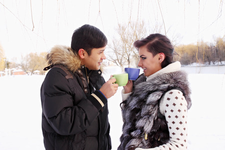 Young couple with a hot drink in winter outdoors photo