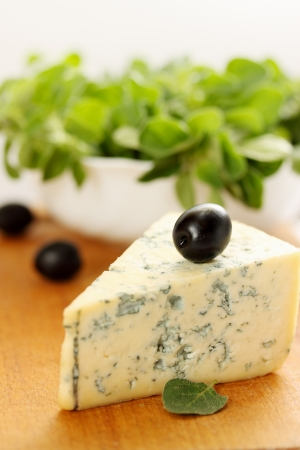 a large piece of blue cheese and black olives photo