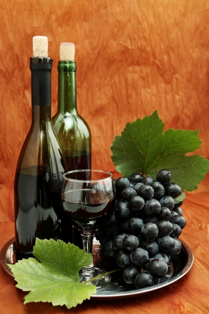 still life with wine bottle, wine glass and grapes photo