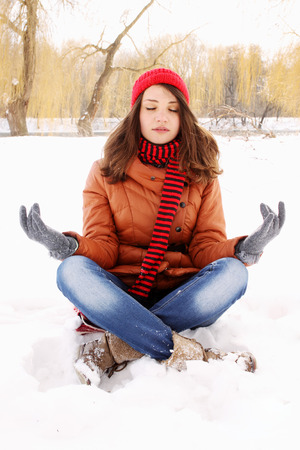 young woman in a lotus position on the snow photo