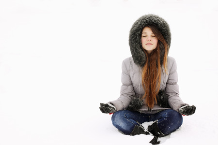 Young girl in lotus pose in the snow photo