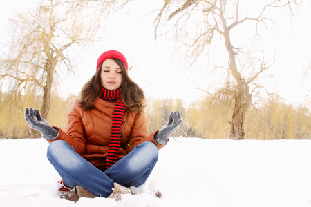 Young girl in lotus pose in the snow