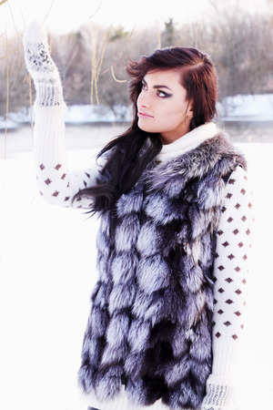 Young beautiful girl in a fur vest catches snow photo