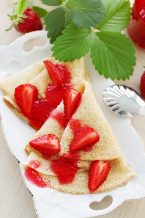 Fried pancakes with fresh strawberries and jam photo