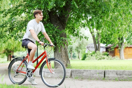 Young handsome bicyclist in a summer park