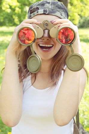 Young woman looking through binoculars on the nature photo