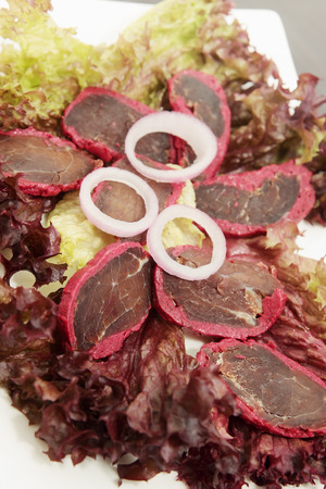 basturma with spices and onions on salad leaves photo