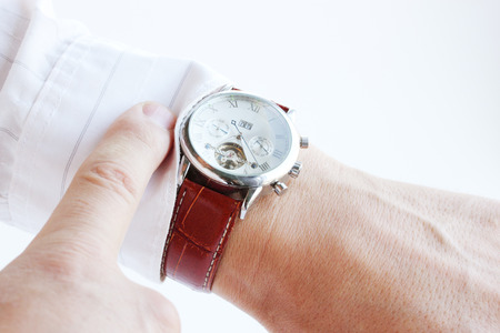 Mens hands, pointing the finger at the clock Stock Photo